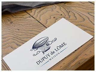 Carte de visite Dupuy de Lôme sur table en bois