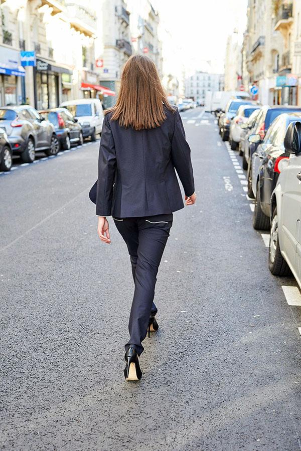 Mannequin femme portant le blazer Femme bleu marine et marchant de dos sur la chaussée. Elle porte le blazer Femme avec une double fente en bas du dos, et un pantalon boyfriend du même tissu bleu marine. Les boutons des poignets des manches du blazer sont en résine bleue.
