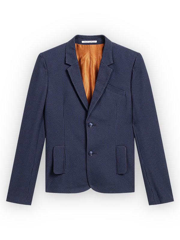 Blazer en tissu coton mélangé italien bleu ardoise et micro-carreaux noirs, ouverture milieu devant à 2 boutons en résine bleue, revers fin, 2 poches verticales à rabats arrondis légèrement, poche poitrine en diagonale cousue à la la main, vue de la doublure intérieure en taille de viscose orange cuivrée et diagonales noires fines, ruban made in France cousue à la main à l'intérieur du pied de col